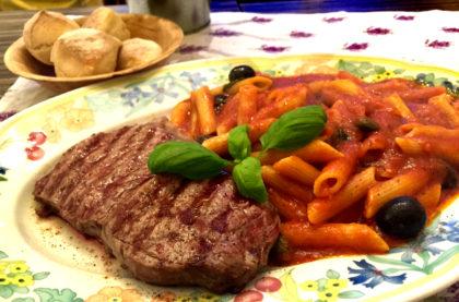 Bistecca vom Grill mit Pasta, Tomatensauce und Oliven